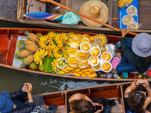Boating through floating market Thailand group trip