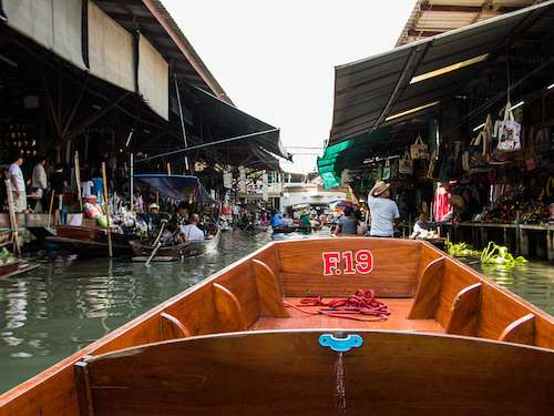 Boating through floating market Thailand group vacation